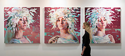 © Licensed to London News Pictures. 15/01/2019. LONDON, UK. A staff member views works by Silvio Porzionato at the  Liquid art system stand. Preview of London Art Fair 2019 at the Business Design Centre in Islington.  The annual fair showcases exceptional modern and contemporary art from the 20th century to present day and opens 16 to 20 January.  Photo credit: Stephen Chung/LNP