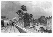 Berkhamsted Station, Hertfordshire, England on the London and Birmingham Railway, c1860. On top of the building on the left is a water tank for supplying locomotives while, on the right, cattle are being driven to the station over a bridge crossing the Grand Junction Canal. The London and Birmingham railway was completed by the autumn of 1838. Robert Stephenson (1803-1859) was the Chief Engineer. Many people opposed the route and forced Stephenson to move the line some distance from their towns. The 112 mile line took 20,000 men 5 years to build. From 'The Land We Live In'. (London, c1860). Engraving.