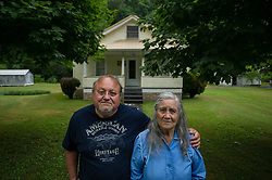 Roger Richmond and his mother, Quinnie, pose outside their home in Lindytown, West Virginia. Lindytown was once home to dozens of families, many with roots dating back generations. In 2008, residents started moving away because of a nearby mine. Today, Roger and Quinnie Richmond are the only original residents that remain. Mountaintop Removal is a method of surface mining that literally removes the tops of mountains to get to the coal seams beneath. It is the most profitable mining technique available because it is performed quickly, cheaply and comes with hefty economic benefits for the mining companies, most of which are located out of state. It is the most profitable mining technique available because it is performed quickly, cheaply and comes with hefty economic benefits for the mining companies, most of which are located out of state. Many argue that they have brought wage-paying jobs and modern amenities to Appalachia, but others say they have only demolished an estimated 1.4 million acres of forested hills, buried an estimated 2,000 miles of streams, poisoned drinking water, and wiped whole towns from the map. © Ami Vitale