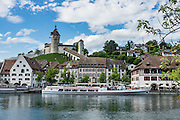 Munot Castle rises above a cruise boat on the Rhine River in Schaffhausen, Switzerland, Europe. Schaffhausen's iconic circular fortress, was built by forced labor in 1564 after the religious wars of the Reformation. A steep stairway climbs from Old Town through vineyards to reach this impressive Renaissance castle. Inside the tower, ascend the spiral staircase for views over a patchwork of rooftops and spires to the Rhine and forested hills. Down in the lower chamber, explore a spectacular, cool vaulted casemate.