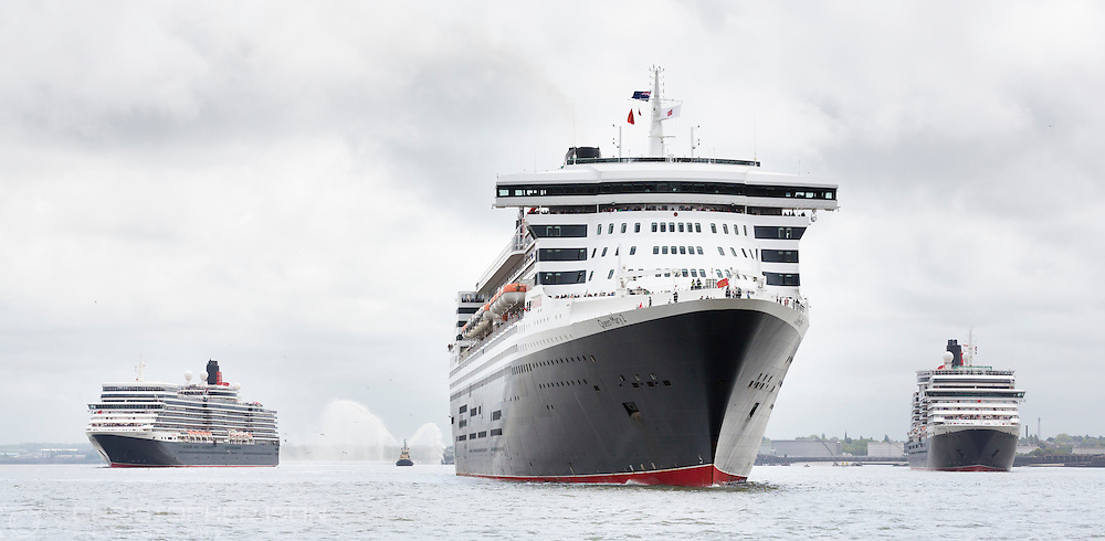 Cunard's fleet gather together in spectacular fashion in Liverpool, its spiritual home, as the company marked its 175th anniversary. Left to right: Queen Elizabeth, Queen Mary 2, and Queen Victoria. The historic lines' three ships, the largest passenger ships ever to muster together on the River Mersey, lined up just 130 metres apart. The vessels lined up three abreast at Liverpool's Pier Head beside its iconic Three Graces: The Royal Liver Building, The Cunard Building and The Port of Liverpool Building. <br /> Picture date Monday 25th May, 2015.<br /> Picture by Christopher Ison. Contact +447544 044177 chris@christopherison.com