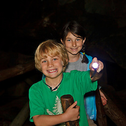 A young brother and sister explore a cave at Lost River Gorge in New Hampshire's White Mountains. North Woodstock.