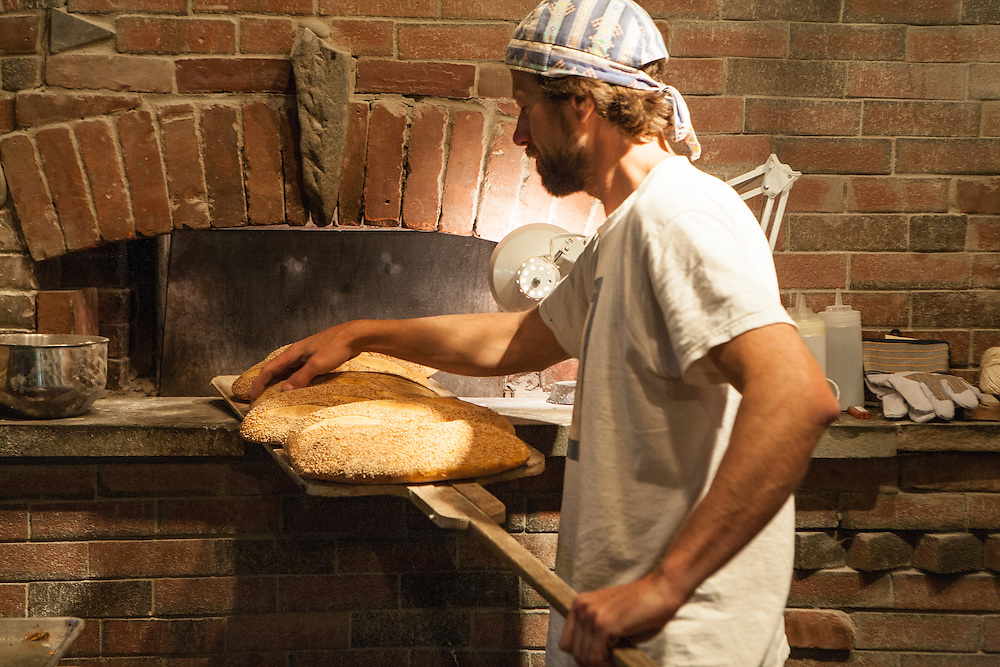 Jamestown, RI - 7 May 2007. Andrea Colognese of The Village Hearth Bakery and Cafe, taking  loaves of bread out of the oven.