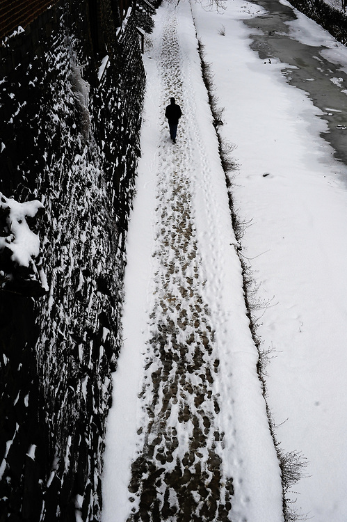 A lone person walks along the frozen C&O canal in Georgetown. Washington, D.C.