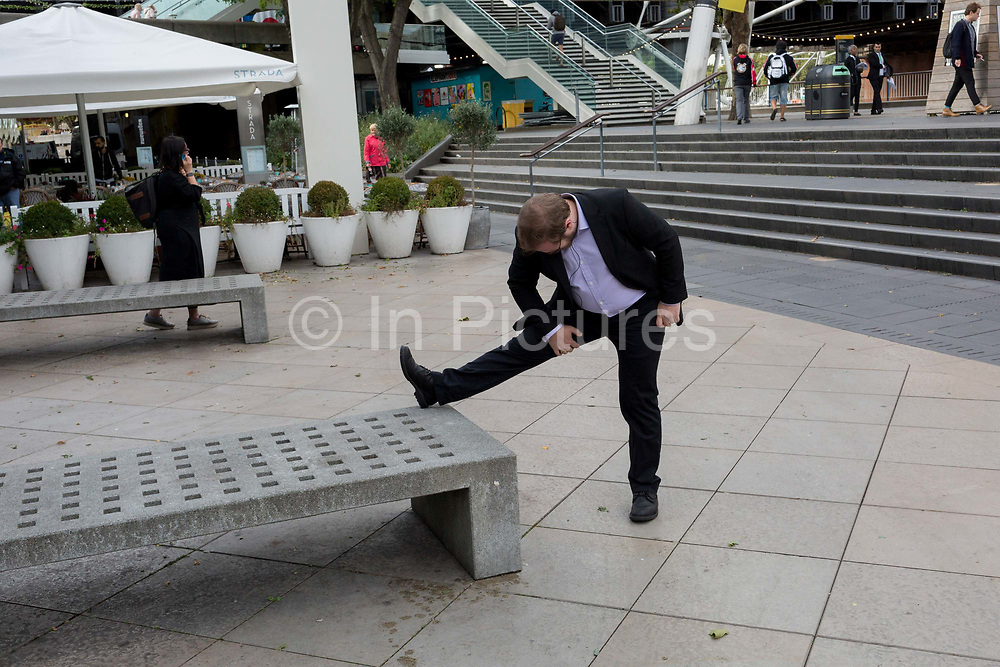 A man wearing a suit spontaneously stretches his hamstring muscle of one leg on the Southbank, on 21st September 2018, in London England.