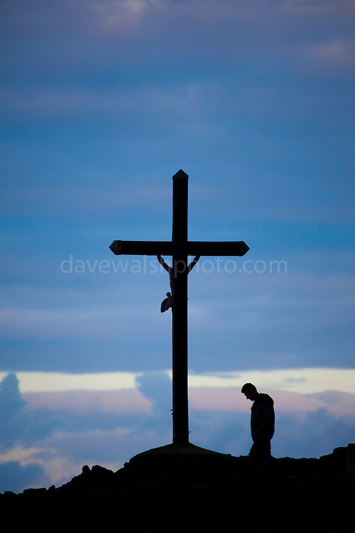 """Man praying at a crucifix beside the  Mediterranean in Collioure, Pyrénées-Orientales, in the Roussillon province in the South of France. This mage can be licensed via Millennium Images. Contact me for more details, or email mail@milim.com For prints, contact me, or click """"add to cart"""" to some standard print options."""