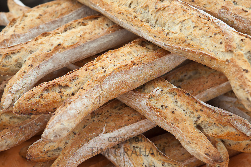 Freshly-baked multigrain 5 cereals French baguette bread on sale at food market at La Reole in Bordeaux region of France