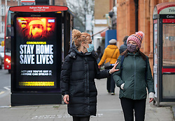 © Licensed to London News Pictures. 08/01/2021. London, UK. Members of the public walk past a 'Stay Home, Save Lives' Covid-19 information display in Fulham, South West London as cases continue to rise dramatically throughout the UK. This week, Prime Minister Boris Johnson plunged England into another lockdown as he ordered schools to close and workers to work from home as the government brings in the army to ramp up vaccinations. Photo credit: Alex Lentati/LNP