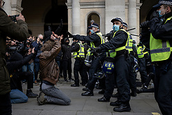 © Licensed to London News Pictures. 03/04/2021. London, UK. A Kill the Bill protester kneels down in front of a line of police in Trafalgar Square. Protests have been held across the UK in opposition to the Police, Crime, Sentencing and Courts Bill which would broaden police powers when dealing with protests. Photo credit: Rob Pinney/LNP