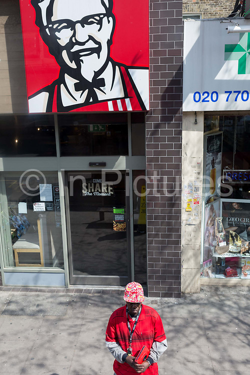 Seen from the window of a London bus, a man in read stands beneath the KFC logo of Colonel Sanders on the Walworth Road in Southwark, south London, on 30th April 2019, in London, England.