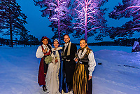 Two  female guests at a Norwegian wedding wearing the bunad, the Norwegian National Costume, stand with the bride and groom  before the reception, Trysil, Norway.