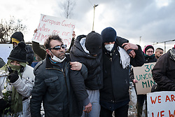 © London News Pictures. Calais, France. 07/03/16. An Iranian man who has been on hugner strike for one week, calling for the intervention of the European Court of Human Rights, is carried through the camp by two friends. French authorities are evicting and demolishing the southern half of the Calais 'Jungle' camp, which charities estimate to contain 3,500 people. . Photo credit: Rob Pinney/LNP