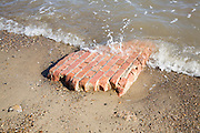 Part of red brick wall eroded and washed by waves, Happisburgh, Norfolk, England