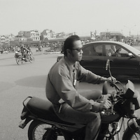 Asia, Vietnam, Hanoi, Motorcycles and traffic fill streets along Yen Phu near Song Hong (Red River) in early morning