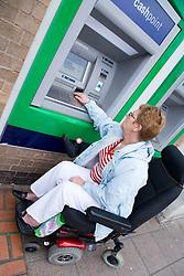 Older woman wheelchair user using a cashpoint machine,