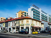 11 DECEMBER 2018 - SINGAPORE:  Traditional shophouses in front of new government housing on Sims Road in the Geylang neighborhood. The Geylang area of Singapore, between the Central Business District and Changi Airport, was originally coconut plantations and Malay villages. During Singapore's boom the coconut plantations and other farms were pushed out and now the area is a working class community of Malay, Indian and Chinese people. In the 2000s, developers started gentrifying Geylang and new housing estate developments were built.      PHOTO BY JACK KURTZ