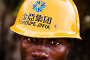 """A Guinean worker wears a helmet from Chinese construction company """"Groupe Jinya"""" on the construction site of the Kipe hospital in Conakry, Guinea on Wednesday March 4, 2009. The Kipe hospital is a 10 million dollars project entirely funded by the Chinese government. (Olivier Asselin for the New York Times)"""