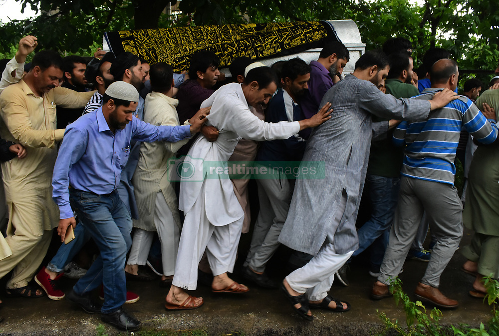 June 15, 2018 - Baramullah, Jammu and Kashmir, India - People carry the coffin of Shujaat Bukhari, slain Editor-in-Chief of the Kashmir Based Local English daily newspaper Rising Kashmir, during his funeral at Kreeri area of Baramullah District of Indian Administered Kashmir. Bukhari was killed after unknown gunmen shot on his vehicle killing Bukhari and two of his Body Guards. However, no Kashmir militant group has claimed the responsibility and has urged United Nations to probe the Killing of the Senior Editor internationally. (Credit Image: © Muzamil Mattoo/Pacific Press via ZUMA Wire)