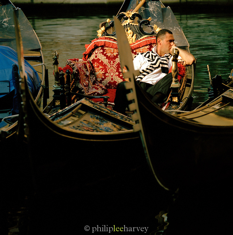 A gondolier sitting and waiting in his gondola, Venice, Italy