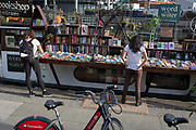 Cyclists stop and browse the titles on sale at Word on the Water, the floating bookshop on the Regent's Canal near Granary Square, on 16th October 2018, in London, England.
