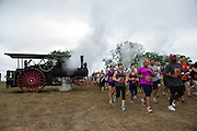 The whistle from an old steam tractor is used to start each wave of runners at the Dirty30 Race in Mulhall, OK.