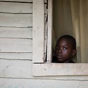A boy looks out of his living room window in the la Cubana area of San Pedro Province in the Dominican Republic, September 12, 2017. The week before he sheltered in the concrete school nearby as Hurricane Irma hit. The area was not badly damaged, though it is prone to diseases, especially now in the rainy season with increased rainfall during the hurricane. Several areas with stagnant water are breeding grounds for mosquitos, increasing cases of dengue, chikungunya, zika and others. stands with two of her seven children in front of their house in the la Cubana area of San Pedro Province in the Dominican Republic, September 12, 2017. The area was not badly hit by Hurricane Irma, though it is prone to diseases, especially now in the rainy season with increased rainfall during the hurricane. Several areas with stagnant water are breeding grounds for mosquitos, increasing cases of dengue, chikungunya, zika and others. The only drinking water available is bought, consuming a large percentage of their weekly budget.