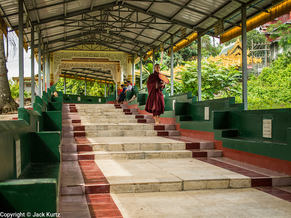 05 JUNE 2014 - YANGON, YANGON REGION, MYANMAR:  A monk walks down a covered walkway at Ngahtatgyi Paya (Pagoda) in Yangon, Myanmar. Yangon, with a population of over five million, continues to be the country's largest city and the most important commercial center.        PHOTO BY JACK KURTZ