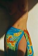 Top part of tropical woman's body being illuminated by shaft of sunlight falling across colorful pareo