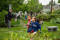 Two young girls run freely through Veteran's Square as folks begin to arrive for the Memorial Day services on Monday morning.  (Karen Bobotas/for the Laconia Daily Sun)