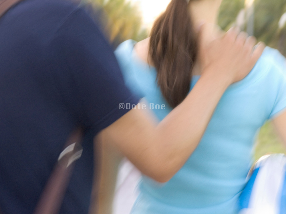 man with his hand on the shoulder of his girlfriend