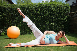 Pregnant woman stretching garden fitness
