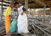 Koh Lanta, Thailand--Two boys show each other the trasures they've found in the debris after a Tsunami destroyed their village of Hua Laem on the island of Koh Lanta in Southern Thailand.  While children approached the slow clean-up process as though is were a treasure hunt, their parents had to deal with the reality of having lost most of their worldly posessions along with their homes and fishing boats. 01/18/05 © Julia Cumes / The Image Works