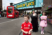 Mother Louise Irwin-Ryan with her daughter Georgia (11, wearing a pink Lolita dress) and son Kiefer (8, wearing a red Liverpool Football Club kit) spending a day out together in Camden Town, North London. Here they are walking near to the famous sign for Camden Lock on the railway bridge. Louise is on various benefits to help support her family income, and housing, although recent government changes to benefits may affect her family drastically, possibly meaning they may have to move out of London. Louise Ryan was born on the Wirral peninsula in 1970.  She moved to London with her family in 1980.  Having lived in both Manchester and Ireland, she now lives permanently in North London with her husband and two children. Through the years Louise has battled to recover from a serious motorcycle accident in 1992 and has recently been diagnosed with Bipolar Affective Disorder. (Photo by Mike Kemp/For The Washington Post)