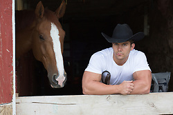 portrait of a rugged cowboy and a horse in a barn