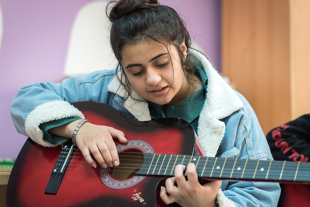 18 February 2020, Amman, Jordan: Sixteen-year-old Ayyan plays the guitar in the Talent Room of Rufaida Al Aslamieh Primary Mixed School in the Sahab district. The school serves more than 1,000 students from kindergarten up to 10th grade, most of them girls from Jordan but also some from Syria and other countries, and, in the lower grades, also boys. With support from the Lutheran World Federation, the school has refurbished its rooms and buildings and introduced a 'Talent Room' in order to nurture the children's creativity. This type of learning environment is otherwise rare in Jordanian public shools.