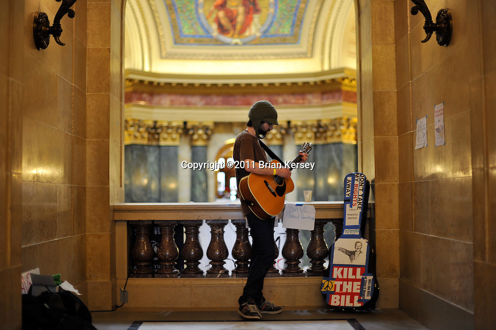 Dan Fransee plays his guitar as protesters occupy the state capitol in Madison, Wisconsin on February 23, 2011. Fransee, of Madison, is there to represent his mother, who is a teacher and was ordered back to work earlier in the week. The Wisconsin budget proposed by Republican Gov. Scott Walker includes cuts in benefits for state workers and takes away many of their collective bargaining rights.     (Photo by Brian Kersey)