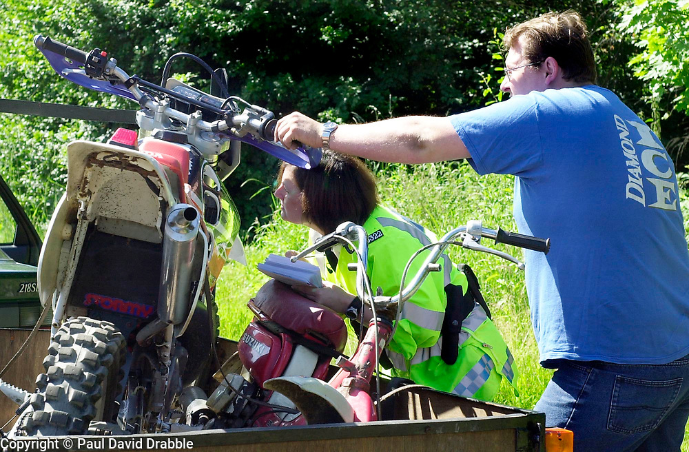 PC Tracy Selwood checks the identification numbers on an off road bike during a police operation aimed at reducing illegal off road biking in the High Green area Sunday <br /><br />Image Copyright Paul David Drabble<br /><br />29 June 2003<br /><br />Copyright  Paul David Drabble<br /><br />[#Beginning of Shooting Data Section]<br />Nikon D1 <br /><br />2003/06/29 09:38:57.2<br /><br />JPEG (8-bit) Fine<br /><br />Image Size:  2000 x 1312<br /><br />Color<br /><br />Lens: 50mm f/1.8<br /><br />Focal Length: 50mm<br /><br />Exposure Mode: Programmed Auto<br /><br />Metering Mode: Multi-Pattern<br /><br />1/180 se