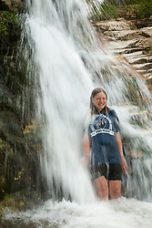 North America, United States, Colorado, Dinosaur National Monument, Green River (Gates of Lodore section), girl standing under waterfall.  MR