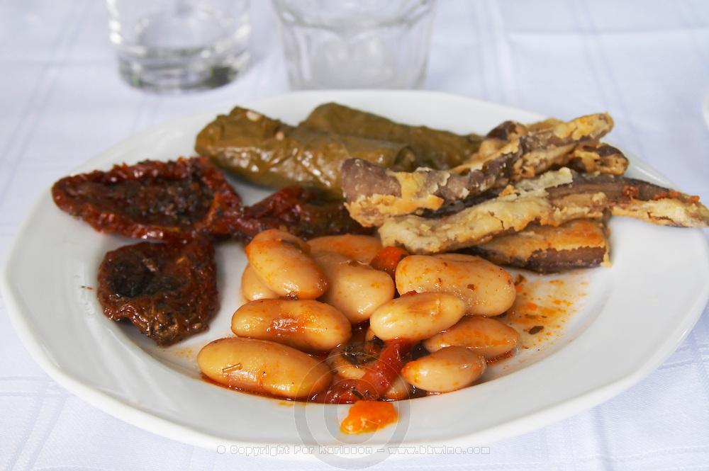Beans, dolma dried tomato. Rakokazano restaurant in Strantza village near Naoussa. Macedonia, Greece.
