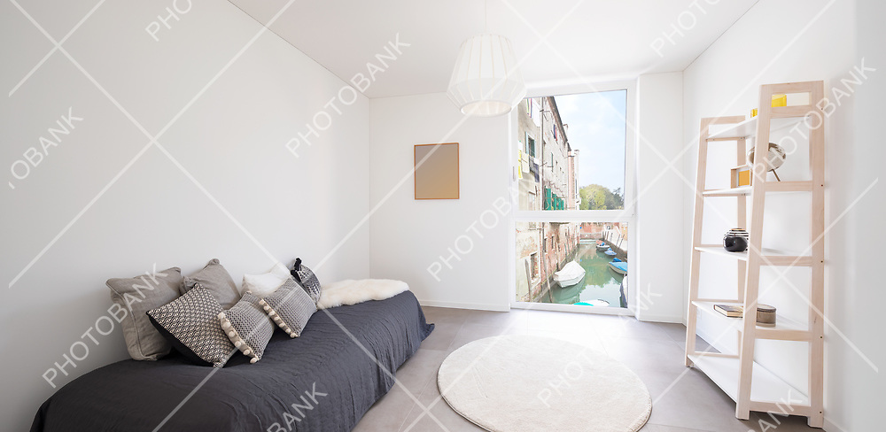 Nice bedroom with bookcase, a bed and lots of pillows. From the window you can see a canal in Venice. Very romantic room. Front view