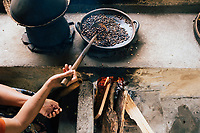 A woman roasts coffee at a small plantation in Ubud in Bali, Indonesia.