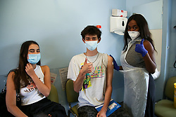 © Licensed to London News Pictures. 23/06/2021. London, UK. 18 year old Alexander Partridge and vaccinator Sally gesture after Sally administered the first dose of the Pfizer Covid-19 to him at a vaccination centre in Haringey, north London. The Government's target is for all over 18s to have been offered a single jab before 19 July. Photo credit: Dinendra Haria/LNP