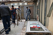 """Moscow, Russia, 14/11/2010..City workers tear down a kiosk with a door sign that reads """"Open 24 Hours"""" near a metro station after new Mayor Sergei Sobyanin ordered the removal of hundreds of the structures, mainly in the city centre. The kiosks, which are ubiquitous throughout the Russian capital, appeared after the fall of the Soviet Union in response to consumer demand and sell a wide range of goods, but most specialise in foodstuffs, alcohol and tobacco."""