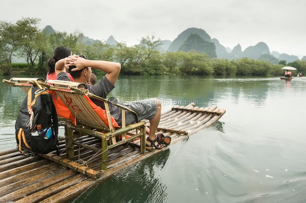 Tourists float down the Li River on a bamboo raft near Yangshuo, China (Model Released, Sean Ouyang, Rachel Ouyang, Tintin Ouyang).