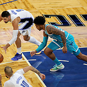 ORLANDO, FL - DECEMBER 17:  Nikola Vucevic #9 of the Orlando Magic grabs a loose ball in front of PJ Washington #25 of the Charlotte Hornets at Amway Center on December 17, 2020 in Orlando, Florida. NOTE TO USER: User expressly acknowledges and agrees that, by downloading and or using this photograph, User is consenting to the terms and conditions of the Getty Images License Agreement. (Photo by Alex Menendez/Getty Images)