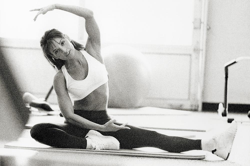Woman doing floor exercises in gym, portrait (B&W, grainy)