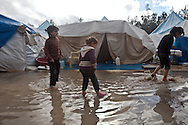 Rita, right wades through the flooded refugee camp to get to her tent. Yayladagi refugee camp for Syrians in southern Turkey. 12/21/2012 Bradley Secker for the Washington Post