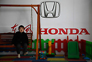 A child of a customer enjoys the swing at the children's play area of a Dongfeng Honda dealership in Shanghai, China, on Monday, 31 January 2011.