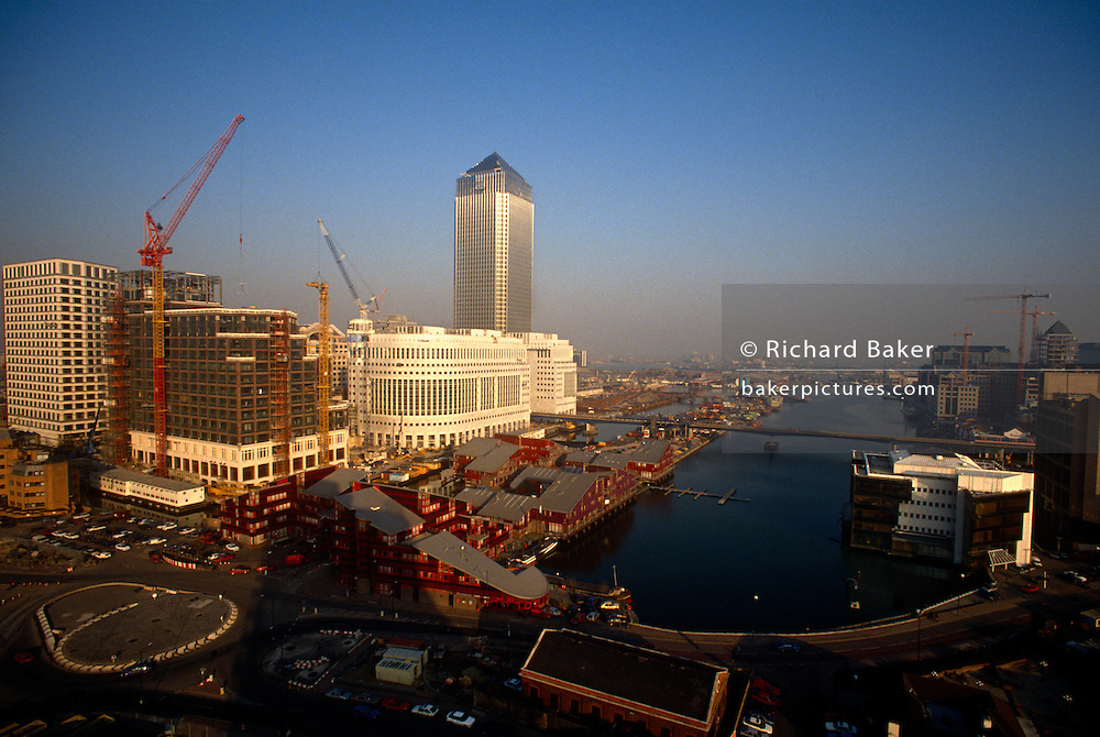A wide panorama aerial landscape of London Docklands in 1991 looking east from a new apartment tower block on the Isle of Dogs. Rising tall is the new Canary Wharf tower (known as 1, Canada Square) soon after its completion - and before the subsequently extensive development phases. This docklands development in east London is the product of the 1980s financial boom when during the office of Prime Minister Margaret Thatcher, huge building projects such as the Docklands consortium saw vast changes in London's landscape. By 2012 Canary Wharf contained 14,000,000 square feet (1,300,000 m2) of office and retail space. Around 90,000 people work here and it is home to the world or European headquarters of numerous major banks, professional services firms and media organisations.