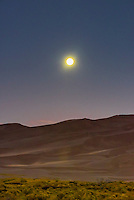 The full moon about to set over the 750 foot tall sand dunes, Great Sand Dunes National Park and Preserve, near Mosca, Colorado USA.